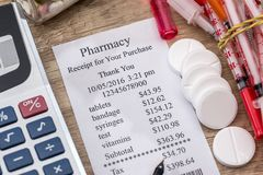 Shopping receipts with pills, calculator. On desk Stock Images