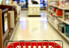 Shopping. Red shopping cart heading towards electronics aisle Royalty Free Stock Photos