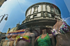 Shopping reflection. Ancient church reflected by a swimwear store window Royalty Free Stock Photo
