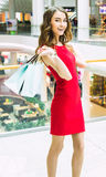 Shopping, sale, christmas and holiday concept - smiling elegant woman in red dress with shopping bags Royalty Free Stock Photos