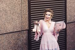 Shopping and sale concept. Attractive young girl in a short pink dress holds in hand`s shoes and bag against the background of roller shutters. Shopping and sale royalty free stock image