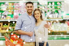 Happy couple with food basket at grocery store Stock Photography