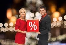 Couple with discount sign over christmas lights stock images