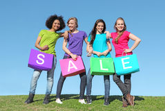 Shopping Sales. Group of happy teens shopping with bags in the sales or sale plain t shirts royalty free stock photography