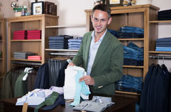 Shopping seller offering various cloths in store. Male shopping seller offering various cloths in store Stock Photo