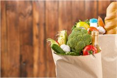 Shopping bags with grocery products on wooden. Shopping shop grocery products bags view close Royalty Free Stock Images