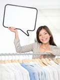 Shopping sign woman. In clothing store. Small clothes business owner with speech bubble sign smiling happy behind clothes rack. Beautiful young Asian Caucasian Royalty Free Stock Photography