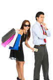 Shopping Smiling Female Removing Money Husband V. A playful smiling female shopper with store shopping bags secretly removing money unnoticed from her pushover Royalty Free Stock Photography
