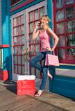 Shopping Spree. Young woman talking on her cell phone after a shopping spree stock images