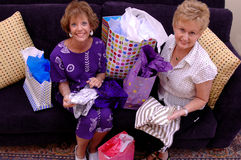 Shopping spree. Two happy senior women with shopping bags and clothes stock photography