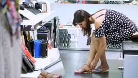 Shopping in the store, shopping. in a shoe store, a girl, Woman sitting on sofa, tries on beautiful sandals. variety of. Summer shoes stock footage