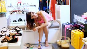 Shopping in the store, shopping. in a shoe store, a girl, Woman sitting on sofa, tries on beautiful sandals. variety of. Summer shoes stock video footage