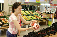 Shopping in supermarket. Woman shopping for fruits and vegetables inside a supermarket Stock Image