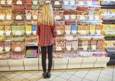 Shopping at the supermarket. Rear view of blond girl picking candies Stock Images