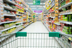Shopping in supermarket shopping cart view with motion blur Royalty Free Stock Image
