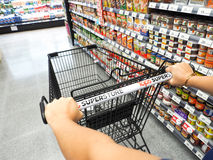 Shopping in supermarket. Shopping trolley and aisle at a top supermarket Stock Image
