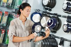 Shopping in supermarket. Woman choosing kitchenware Royalty Free Stock Images