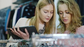 Shopping with the tablet. Two women look things in a clothing store, use your tablet. Two young woman make purchases in a clothing store. Enjoy your tablet, look stock video