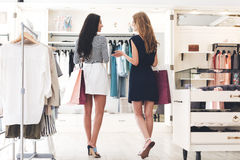 Shopping therapy in action. Rear view of two beautiful women with shopping bags looking at each other with smile while walking at the clothing store Royalty Free Stock Photos