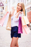 Shopping therapy. Beautiful young cheerful woman holding shopping bags and looking at camera while standing outdoors Royalty Free Stock Images