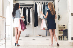 Shopping therapy with friend. Rear view of two beautiful women with shopping bags looking at each other with smile and picking clothing while standing at the Stock Photos