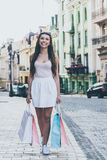 Shopping therapy. Full length of beautiful young woman carrying shopping bags and looking at camera with smile while walking along the street Stock Photos