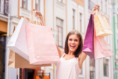 Shopping therapy makes her happy. Attractive young woman holding shopping bags and smiling while standing outdoors Stock Photo