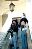 Shopping time. Girlfriends riding the escalator in the mall. Going shopping. Women laughing and smiling as they look at other people Royalty Free Stock Photo