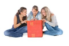 Shopping Time!. Three girls with shopping bag looking into it Royalty Free Stock Photos