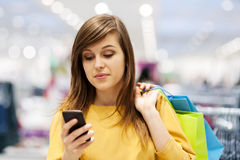 Shopping time. Young woman texting on mobile phone in store Royalty Free Stock Image