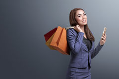 Shopping time, asian woman with smartphone holding shopping bags Stock Image