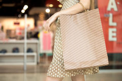 Shopping time concept. Close-up of young pretty long-haired woman wearing summer beige polka dot dress walking in shopping mall holding shopping bag. Fashion Royalty Free Stock Photo