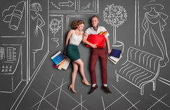 Shopping time. Love story concept of a romantic couple on shopping against chalk drawings background. Young happy couple standing together with shopping bags in royalty free illustration