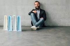Shopping time urban lifestyle young man bags. Exciting shopping . Urban lifestyle. Happy young bearded man sitting on floor with bags. Copy space for advertising stock photo