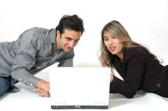 Shopping Togther. A Happy Diverse couple on white background sharing the computer and doing internet shopping Royalty Free Stock Photos