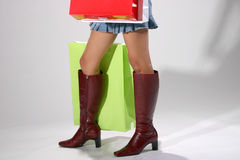 After a shopping trip. Legs of woman in boots with shopping bags royalty free stock photos