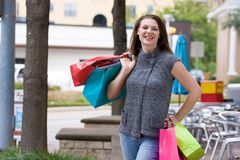 Shopping Trip. Attractive young happy woman with colorful shopping bags walking in an urban city environment Stock Photos