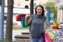 Shopping Trip. Attractive young happy woman with colorful shopping bags walking in an urban city environment Royalty Free Stock Photos