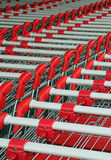 Shopping troleys. Parked shopping trolleys, red and grey color Royalty Free Stock Photos