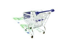 Shopping trolley on 100 euro notes isolated. On white background Stock Photos