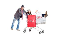Shopping trolley. Cheerful couple with a shopping trolley. Isolated over white background Stock Photography