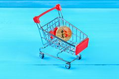Shopping trolley cart with Coins bitcoin, buying goods for crypto currency. Shopping trolley cart with Coins bitcoin, buying goods for crypto currency Stock Photos