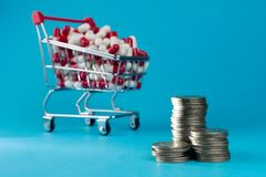 Shopping trolley cart filled red medicinal capsules royalty free stock images