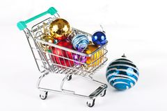 Shopping trolley with Christmas decorations isolated on white. Shopping trolley with Christmas decorations. Concept: preparation for the Christmas holiday Royalty Free Stock Photography