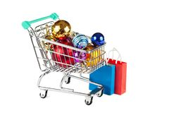 Shopping trolley with Christmas decorations and paper bags isola. Shopping trolley with Christmas decorations and paper bags. Concept: preparation for the Royalty Free Stock Photography