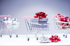 Shopping trolley with christmas gift. Gift box with red ribbon  on a white background. Christmas decoration. Shopping trolley with christmas gift. Gift box with Stock Photo
