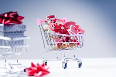 Shopping trolley with christmas gift. Gift box with red ribbon  on a white background. Christmas decoration. Shopping trolley with christmas gift. Gift box with Royalty Free Stock Photography