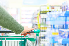 Shopping trolley. Close up of women hand pushing shopping trolley in supermarket Royalty Free Stock Photo