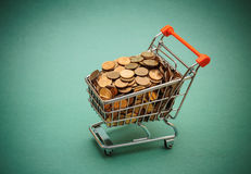 Shopping trolley with coins. On a green background Stock Photos