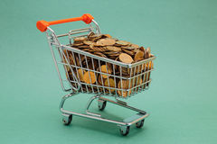 Shopping trolley with coins. On a green background Royalty Free Stock Image